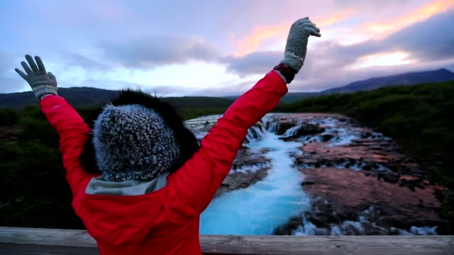 asian woman enjoy view at waterfall in iceland, slow motion - non profit organization stock videos & royalty-free footage
