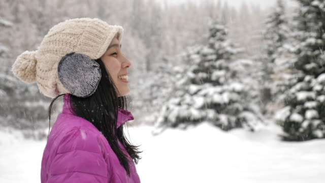 asian woman enjoying a snowy in winter forest - snowflake stock videos & royalty-free footage