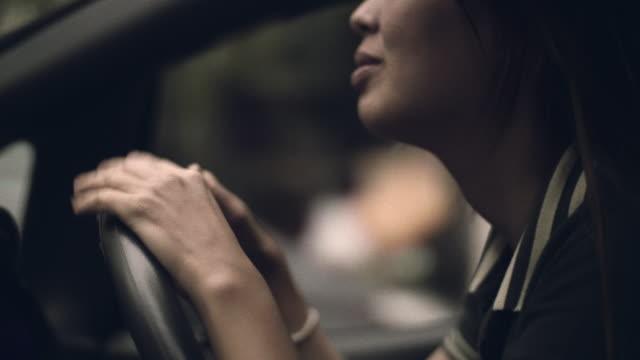 vidéos et rushes de femme asiatique, appréciant la musique dans la voiture - écouter