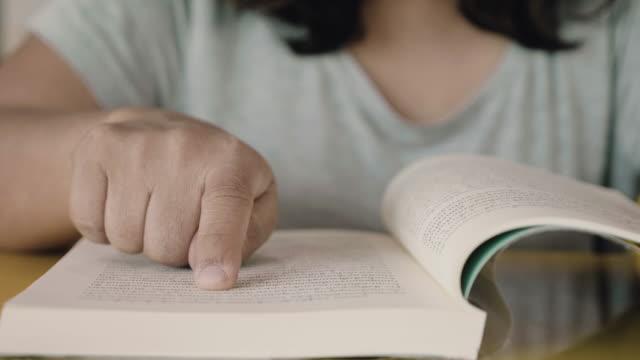 donna asiatica che si diverte a leggere un libro in ufficio. - letteratura video stock e b–roll