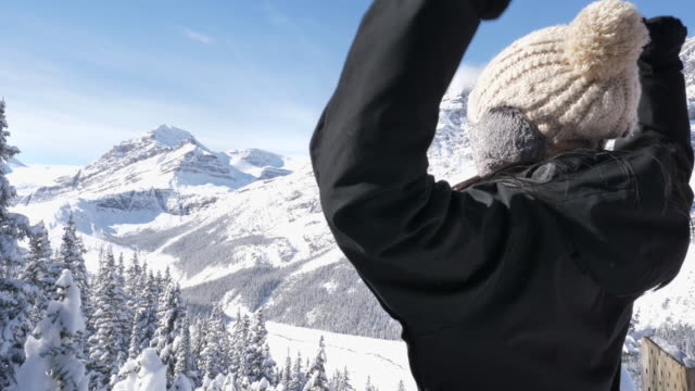 asian woman enjoying view of moraine lake in winter at canada - leisure activity stock videos & royalty-free footage