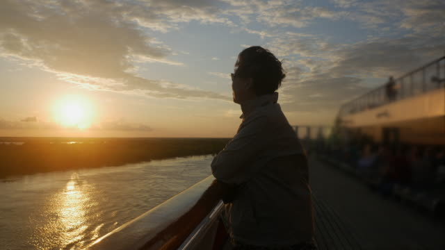 asian woman enjoys sunset view on board cruise ship - cruise stock videos & royalty-free footage