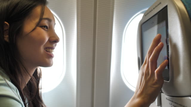 asian woman entertainment on airplane - arts culture and entertainment stock videos & royalty-free footage