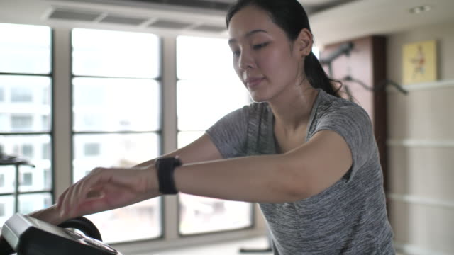 asian woman exercise cycling in gym and using smart watch for tracking plus - exercise bike stock videos & royalty-free footage