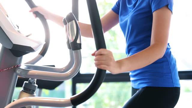 楕円形のマシンクロストレーナーで運動するアジアの女性 - 女性選手点の映像素材/bロール