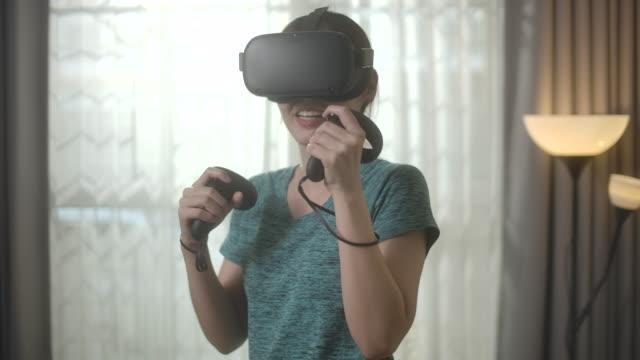 asiatische frau trainieren mit spielen vr brille spiel zu hause, zeitlupe - schutzbrille stock-videos und b-roll-filmmaterial