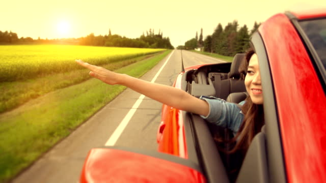 asian woman experiences freedom on the highway - convertible stock videos & royalty-free footage