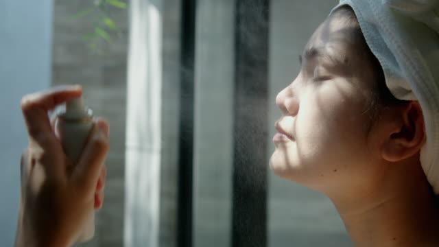 ミネラルウォータースプレーでアジアの女性顔の治療。 - 純水点の映像素材/bロール