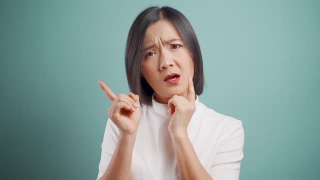 asian woman feel confused pointing finger left or right looking at camera isolated over blue background. 4k video. emotional conceps. - man made object stock videos & royalty-free footage