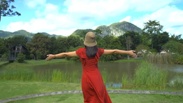 vidéos et rushes de femme asiatique n'hésitez pas courir dans les vastes champs de fleurs par temps clair dans la forêt. - bras humain