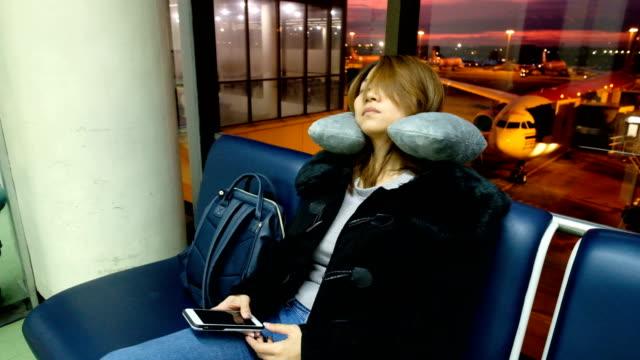 vídeos de stock e filmes b-roll de a asian woman fell asleep on chair at international airport terminal. passengers of transfer flight waiting for boarding - aviation fatigue