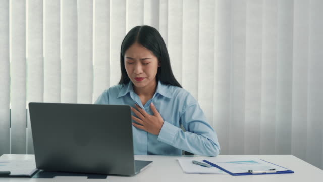 asian woman felt pain in her chest while sitting at work. - myocardium stock videos & royalty-free footage