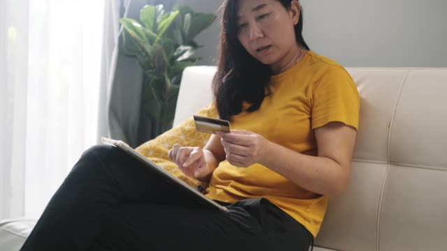 asian woman filling credit card details after home shopping online at home. - home shopping stock videos & royalty-free footage