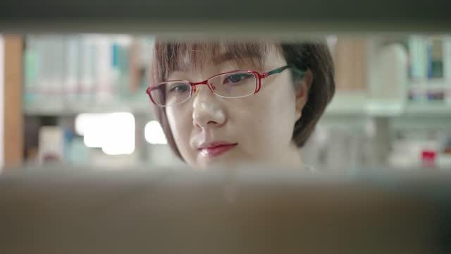 vidéos et rushes de femme asiatique trouvant et lisant un livre sur l'étagère de la bibliothèque - littérature