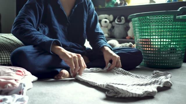アジアの女性は、ベッドの上の洗濯物の折りたたみ。 - たたむ点の映像素材/bロール