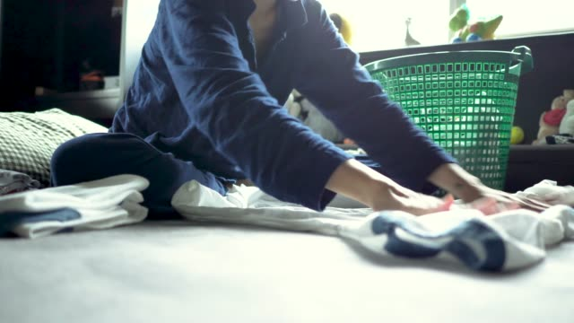 asian woman folding laundry on the bed. - chores stock videos & royalty-free footage