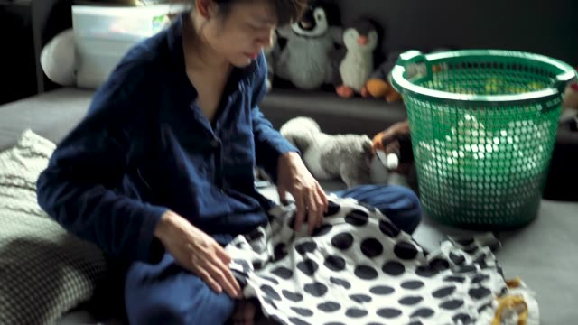 asian woman folding laundry on the bed. - folding stock videos and b-roll footage
