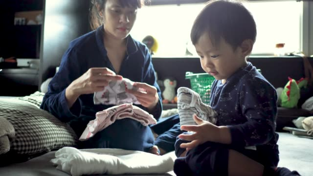 asian woman folding laundry watching playful baby boy playing. - washing stock videos & royalty-free footage