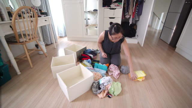 自宅の楽屋でベビークロスを折りたたむアジアの女性 - 洗濯かご点の映像素材/bロール