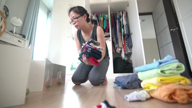 asian woman folding the baby cloth in the dressing room at home - hamper stock videos & royalty-free footage