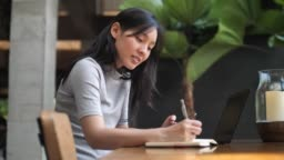 Asian woman freelance working in Cafe with Smart phone for ordering online form her customer