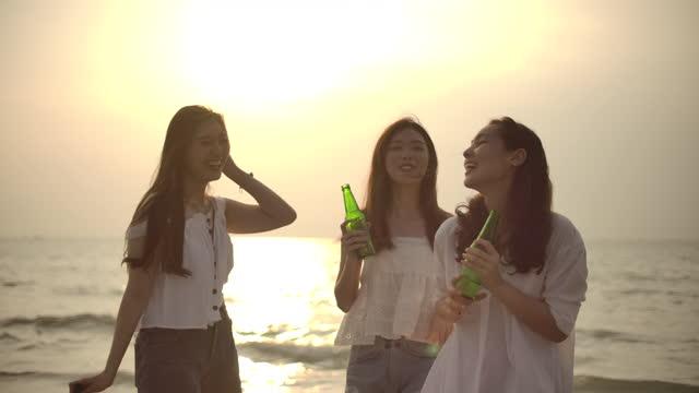 vidéos et rushes de ami de femme asiatique ayant la partie de coucher du soleil sur la plage - party social event
