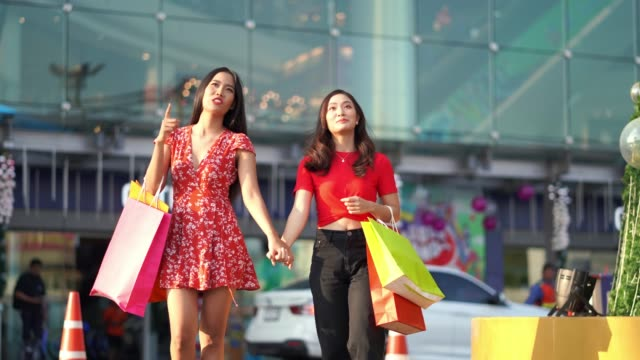 asian woman friend they are shopping at the mall. happily - bag stock videos & royalty-free footage