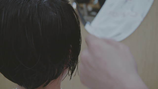asian woman getting her hair cut and styled at a salon. - short hair stock videos & royalty-free footage