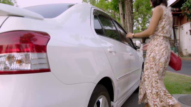 白人車に入るアジアの女性。 - 交通輸送点の映像素材/bロール