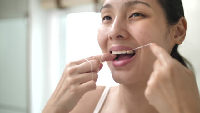 asian woman getting ready to floss her teeth in her bathroom at home - plaque bacteria stock videos & royalty-free footage