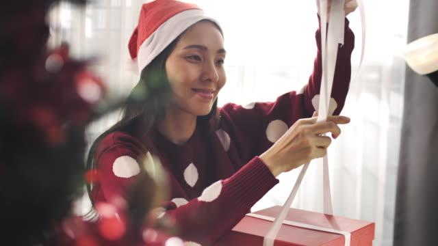 stockvideo's en b-roll-footage met aziatische vrouw gift wrapping kerst - cadeau
