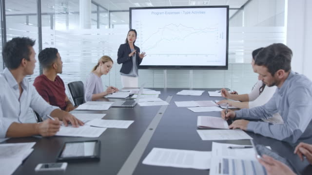 asian woman giving a financial presentation in the conference room - sala conferenze video stock e b–roll