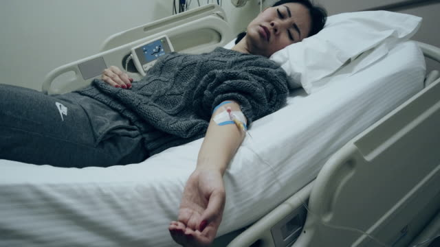 asian woman got coronavirus covid-19 quarantine. having an iv drip at hospital - citochinesi video stock e b–roll