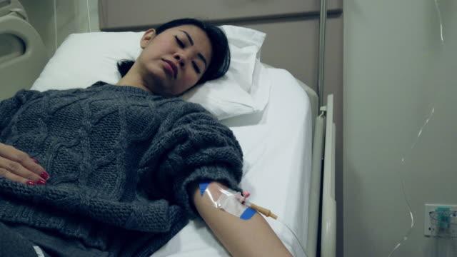 la donna asiatica ha ottenuto la quarantena covid-19 del coronavirus. avere una flebo iv in ospedale - citochinesi video stock e b–roll