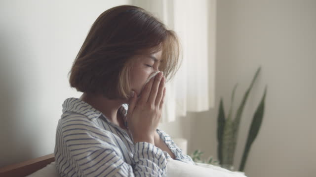 asian woman got flu sneezing in tissue sit on bed - problems stock videos & royalty-free footage