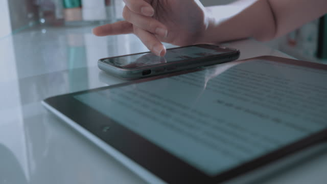 asian woman hand reading e-book on her tablet at home - e book stock videos & royalty-free footage