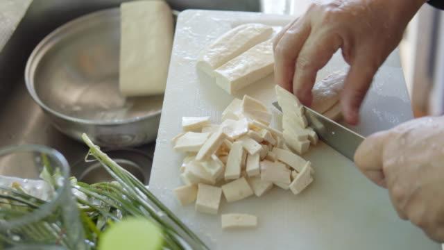 stockvideo's en b-roll-footage met aziatische vrouw hand snijden een tofu in de keuken - dairy product
