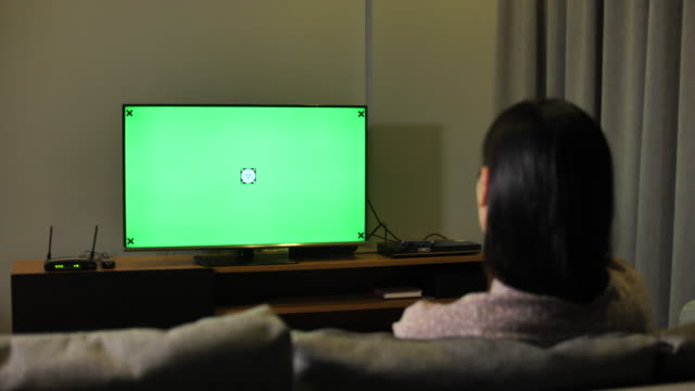 asian woman hand with tv remote switching channels on a green screen tv - changing channels stock videos & royalty-free footage