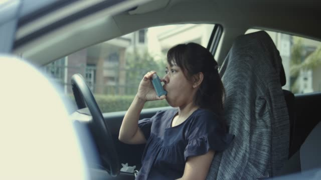 Asian woman having asthma attack in the car