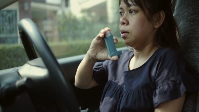 asiatische frau mit asthma im auto angreifen - wohngebäude innenansicht stock-videos und b-roll-filmmaterial