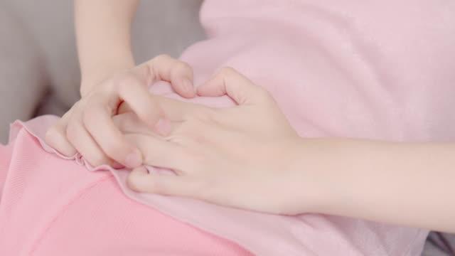 stockvideo's en b-roll-footage met aziatische vrouw met bekkenpijn buikpijn terwijl liggend op een bank thuis - romp lichaamsdeel