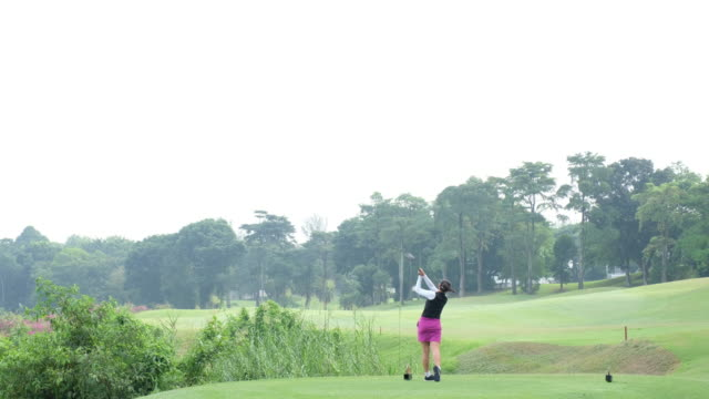 asian woman hits a great golf shot - golf swing women stock videos & royalty-free footage