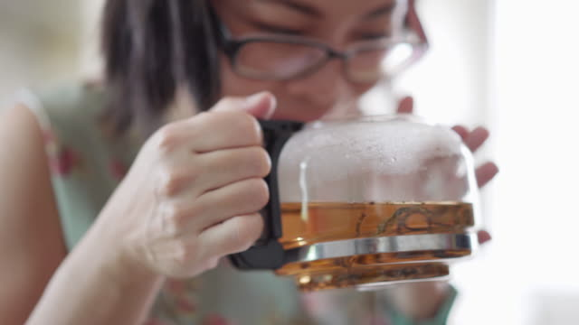 asian woman holding a teapot and smelling the aroma of hot tea for relaxation at home - steep stock videos & royalty-free footage