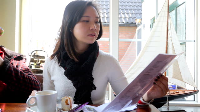 asian woman holding menu sheet for order - menu stock videos & royalty-free footage