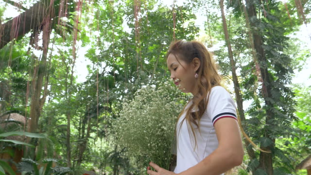Asian Woman Holding White Flowers Standing In Nature