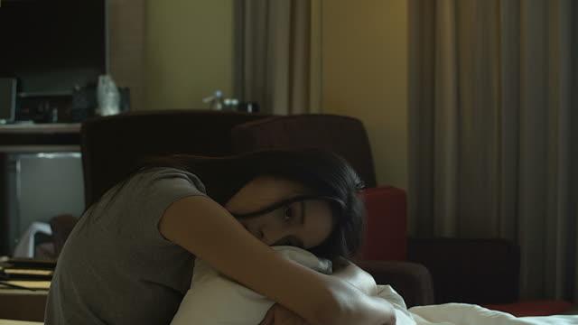 4K: Aziatische vrouw haar knieën knuffelen tot haar borst in bed