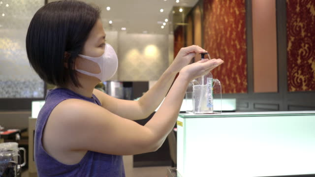 asian woman in a protective mask using alcohol as hand sanitizer after eaten some food with family at the restaurant - rubbing alcohol stock videos & royalty-free footage