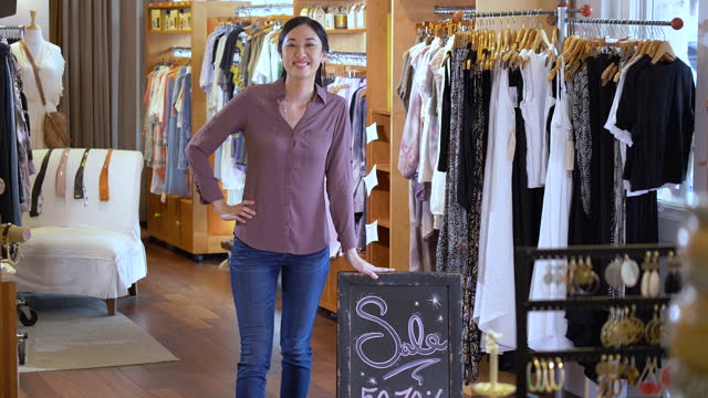 asian woman in boutique next to sale sign smiling - hand on hip stock videos & royalty-free footage
