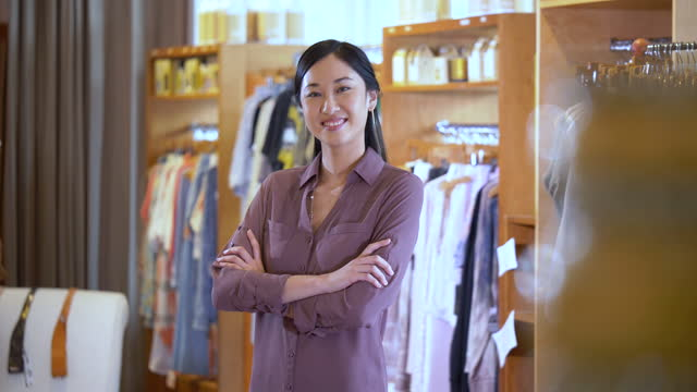 asian woman in boutique smiling at camera - hand on hip stock videos & royalty-free footage