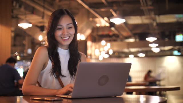 asian woman in casual clothing using laptop for her work - e mail video stock e b–roll